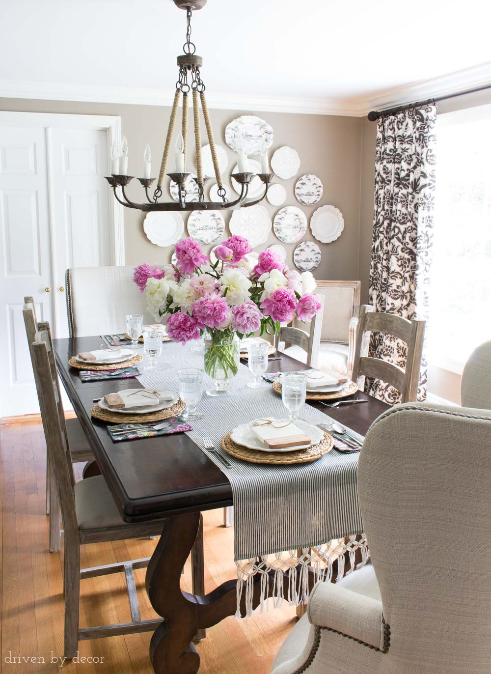 Classic dining room with dark gray walls, rope chandelier, ladder back side chairs, wingback end chairs, and decorative plate wall
