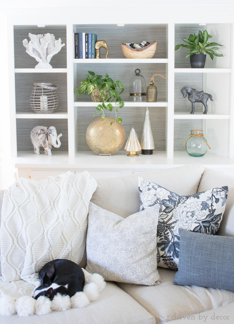 Back of bookcase lined with grasscloth wallpaper - love that added texture and rich touch it adds to this space! More ideas for what to do with the back of bookcases in this post!