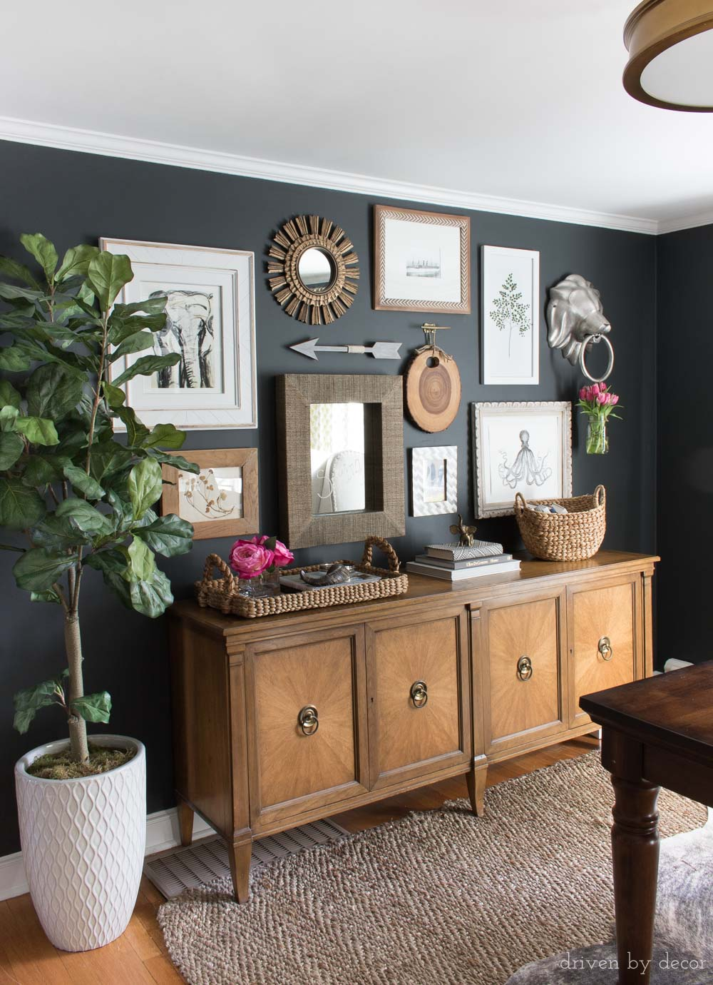 Love the mix of art and mirrors in this gallery wall hung on black walls with brass room accents