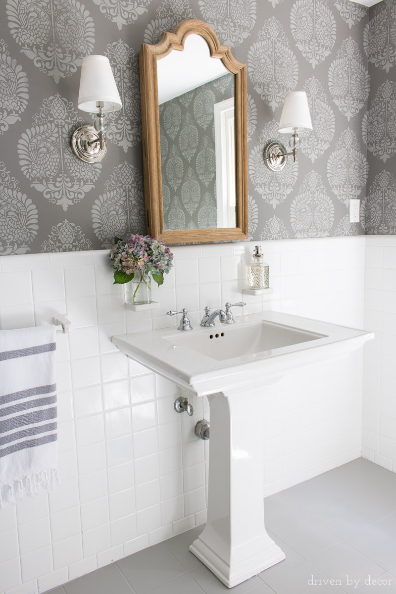 LOVE this bathroom makeover with stenciled walls that look like wallpaper, wood medicine cabinet, twin sconces, and painted tile floors!