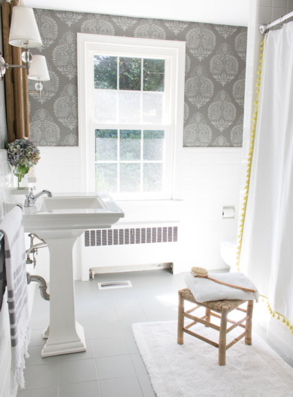 A budget bathroom remodel with ceramic tile floors painted gray and walls stenciled to look like wallpaper. Bathroom includes pedestal since, wood medicine cabinet, twin sconces, and tasseled shower curtain.