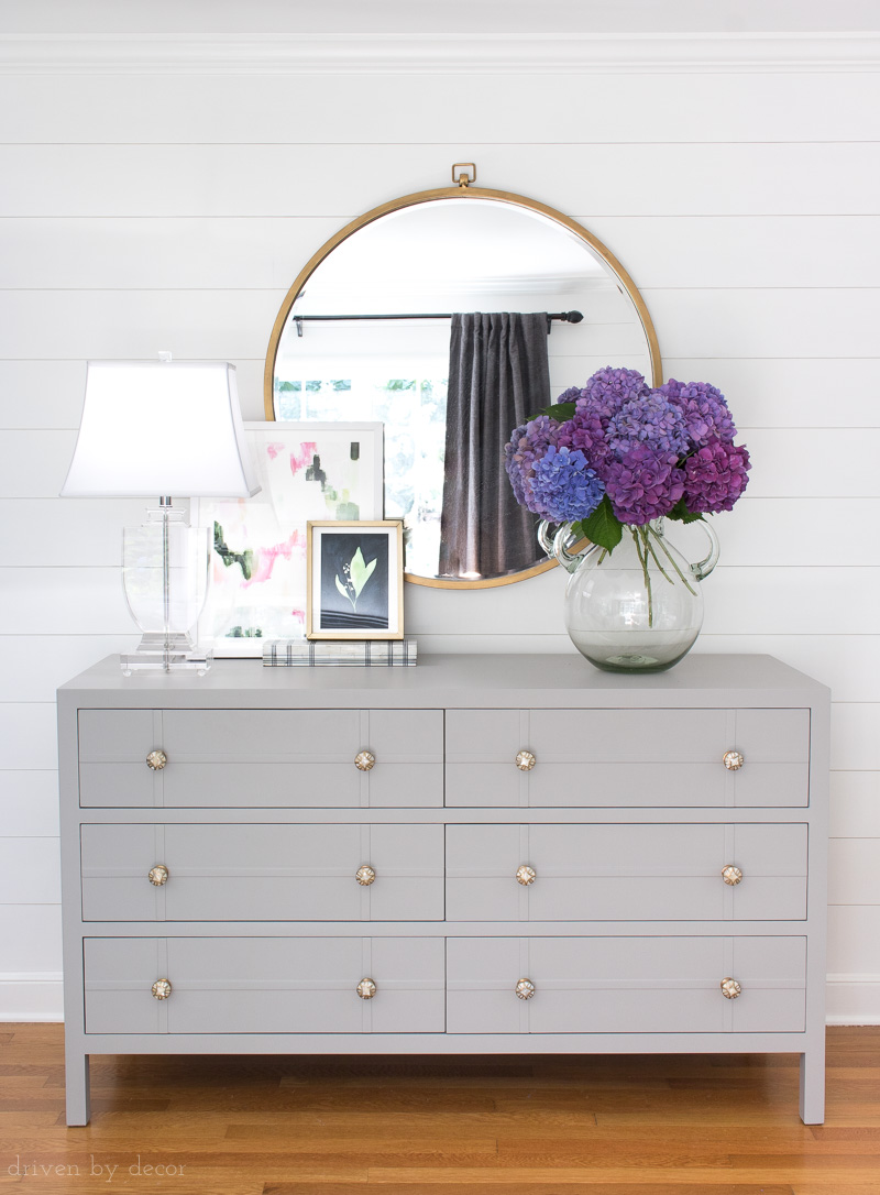 Love this simple arrangement of a large round mirror, crystal lamp, layered art, and huge bouquet on a painted gray dresser!