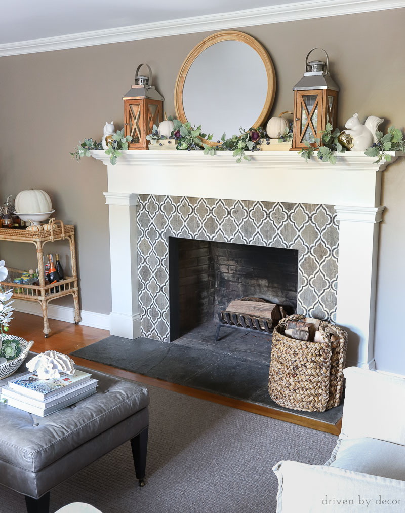 Fireplace decorated for fall with twin lanterns, pumpkins, faux greenery, and the cutest ceramic squirrels!