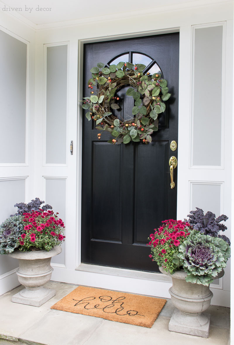 Simple fall porch decor - planters filled with cabbages, kale, and mums and a large rose hip wreath!