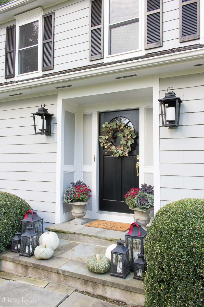 Ideas for decorating your front porch for fall! Planters with mums, cabbages, and kale, lantern trios, and rose hips wreath.