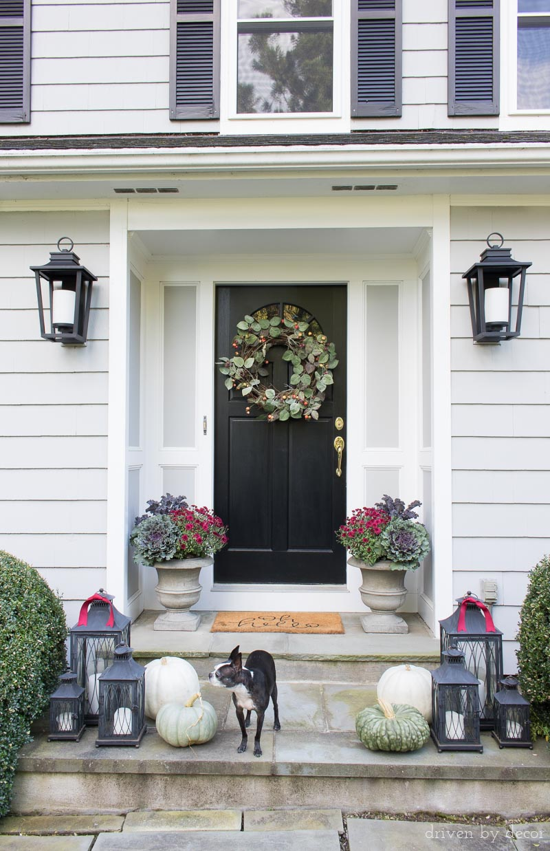 Our fall front porch with black lantern sconces, fall wreath, and planters filled with cabbages, kale, and mums. Part of a New England fall home tour!