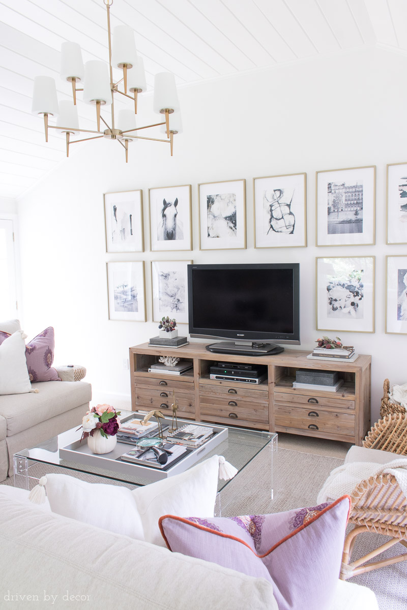 Loving this family room decorated for fall with plum home accessories! And that art wall around the TV!!