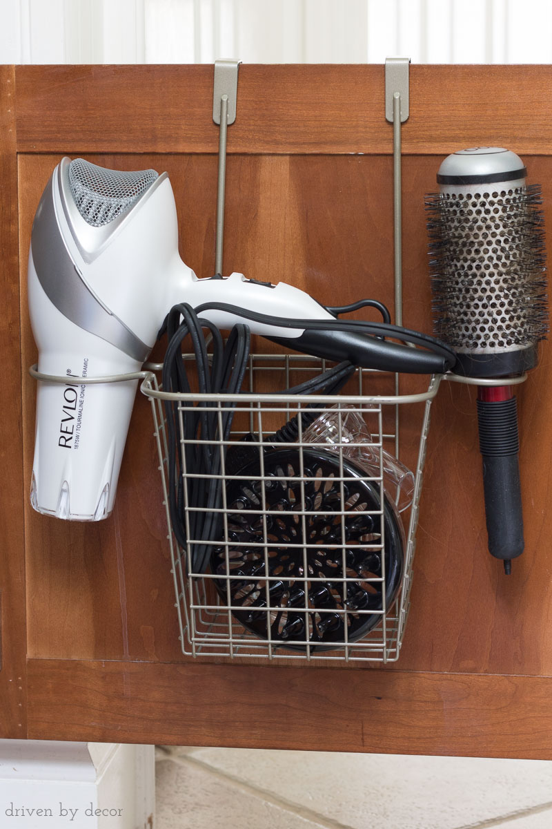 The perfect solution for storing your hair dryer! This caddy hangs on the back of the cabinet and has a holder for the hair dryer, a brush or curling iron, and a basket for the cord and accessories!