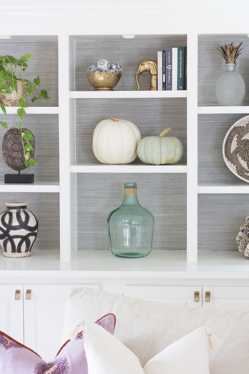 Built-in bookcases with grasscloth back - simple styling of shelves (including pumpkins for fall!)