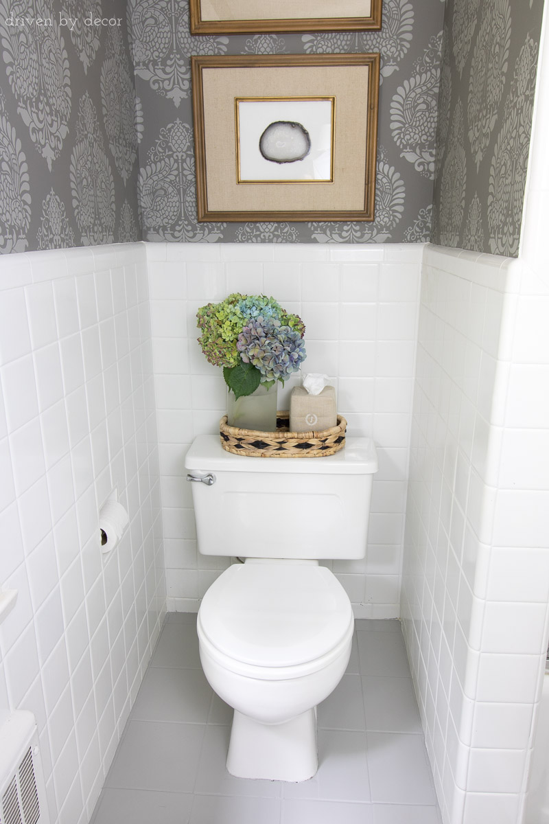 Budget bathroom makeover, with stenciled walls (yep, that's not walllpaper!), painted ceramic tile floors, DIY art, and more!