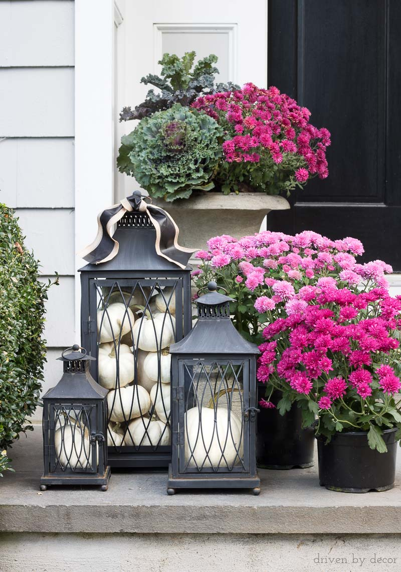 Love this trio of black lanterns filled with pumpkins (and the mums too!) for a fall front porch
