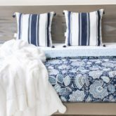 Beautiful blue and white floral quilt, striped tassel pillows, and white pom pom throw