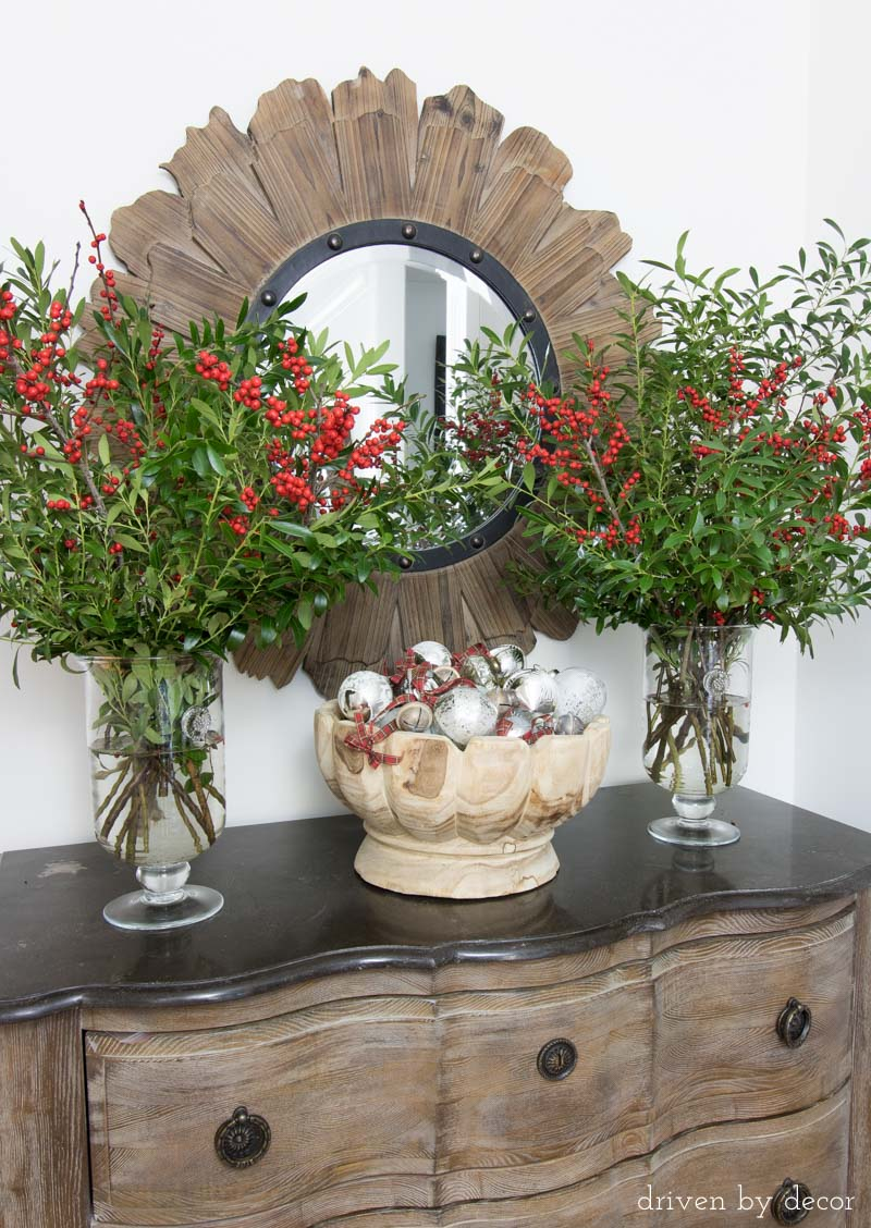 Branches clipped from backyard bushes plus berry bundles and a bowl full of ornaments make beautiful, simply entry way decor for Christmas.
