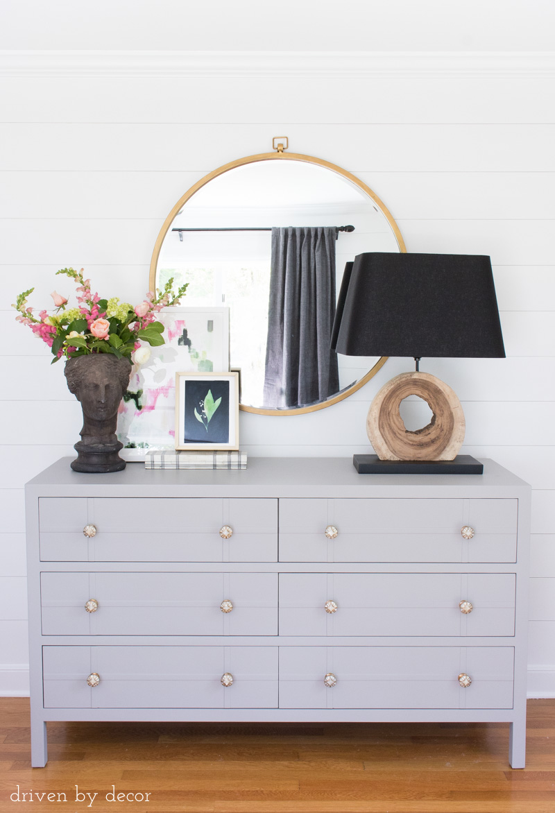 Love this One Room Challenge master bedroom makeover! Shiplap walls, painted dresser, large round mirror, and layered art!