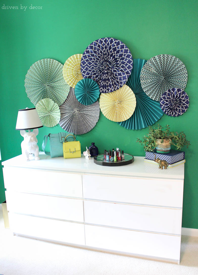 Simple and inexpensive wall art for decorating a kid's room - paper rosettes! Post includes link to simple tutorial to show you how to make them!