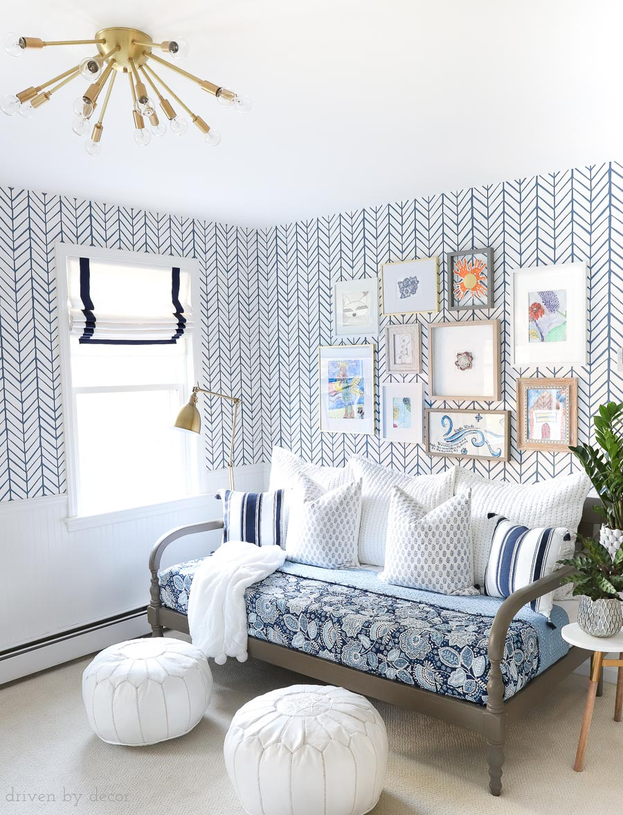 Fun bonus room space with daybed for lounging (that will also be used as a guest bed), kids art gallery wall, blue and white wallpaper and bedding, Moroccan poufs, Roman shades, and brass sputnik light fixture!