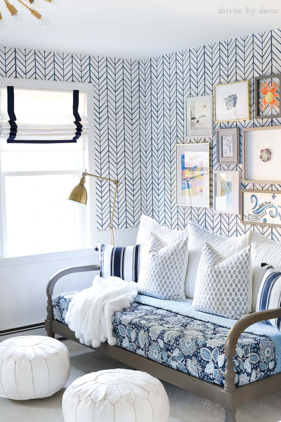 Blue and white bonus room area with daybed, blue floral quilt, blue and white pillows, white leather Moroccan poufs, Roman shades, and an art gallery wall!
