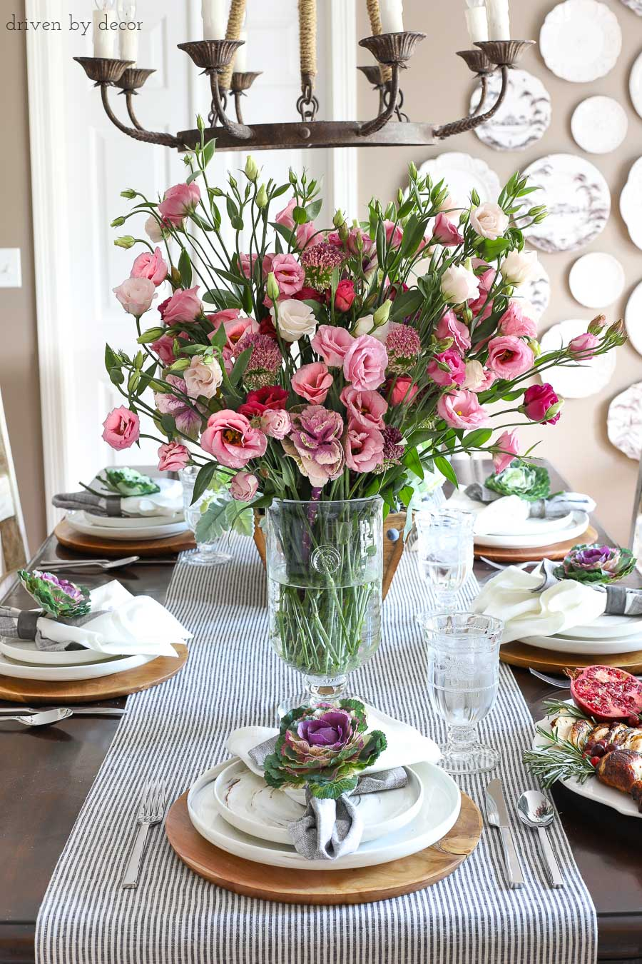 Simple dining room table setting for Thanksgiving with fresh flowers for a centerpiece and faux kale tucked into napkins