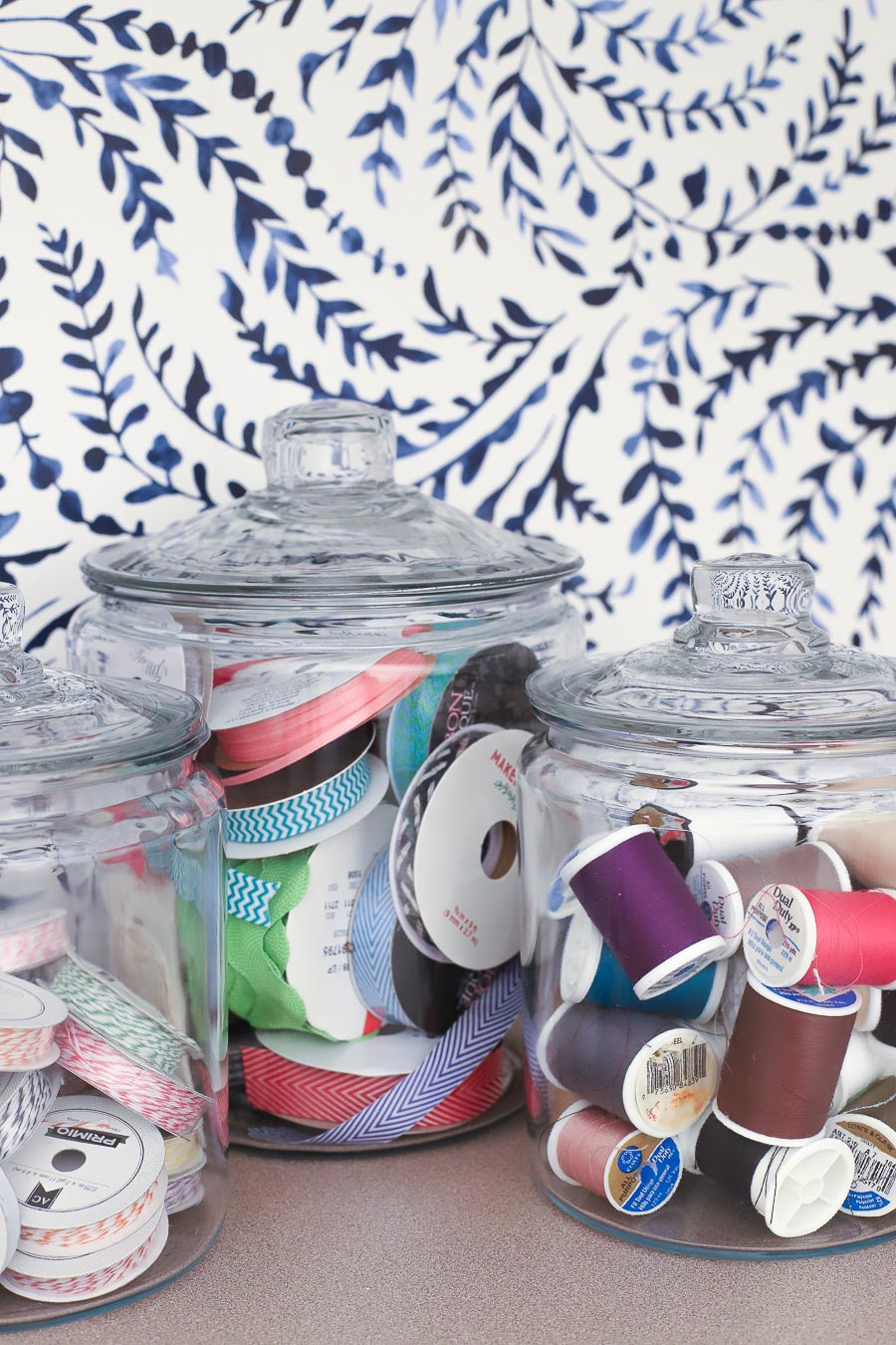 Glass storage jars hold ribbons and thread in this cute craft room!
