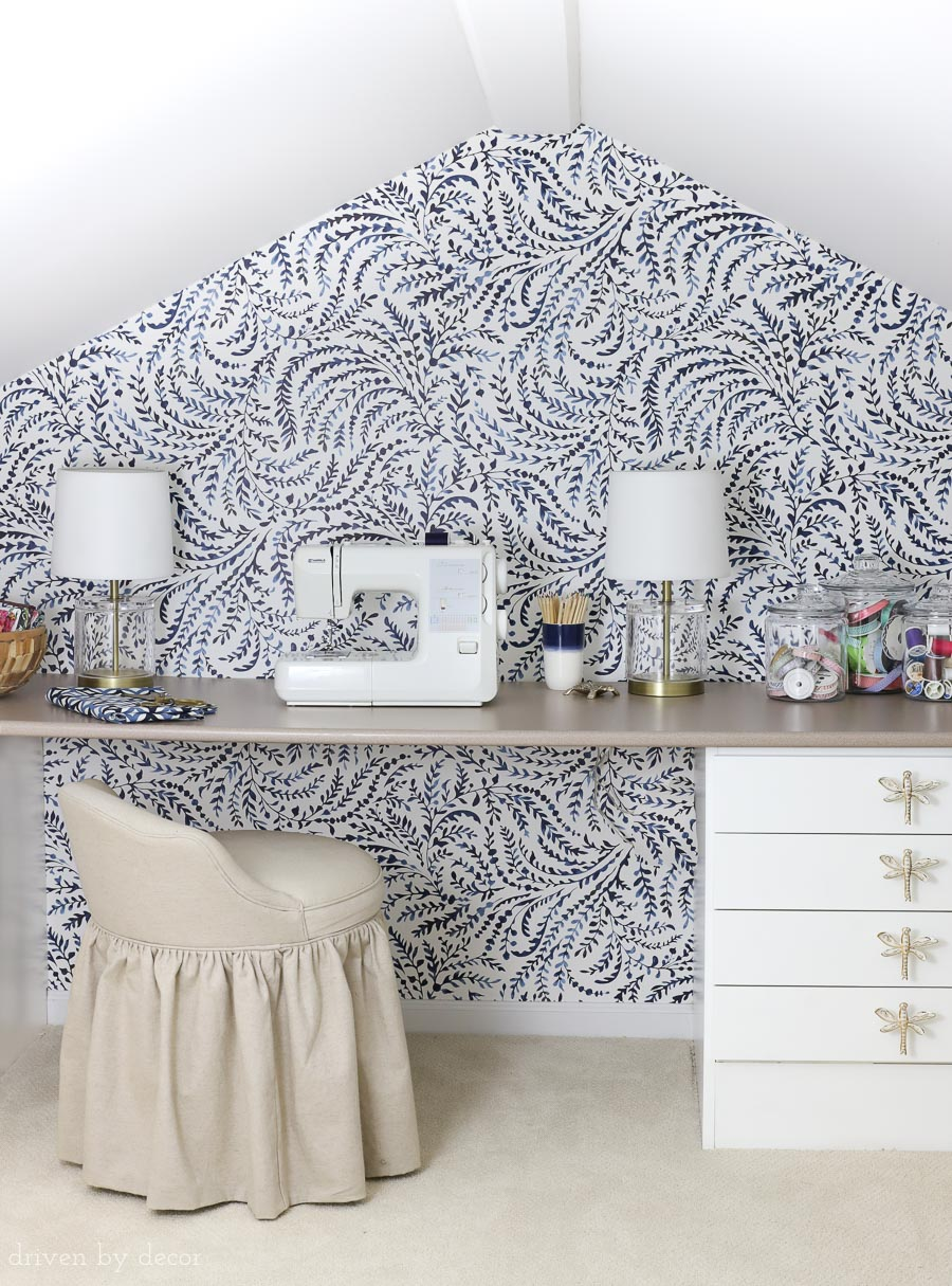 Such a cute kids craft room! Love the blue and white feather wallpaper and the brass and acrylic lamps!
