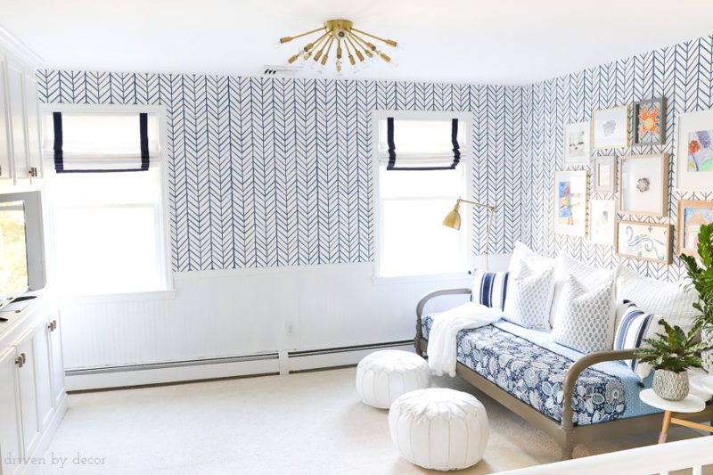 Bonus room / loft area for teens decorated with blue and white herringbone wallpaper, Roman shades, brass lighting, a daybed, gallery wall, and more! Click over for all of the details!