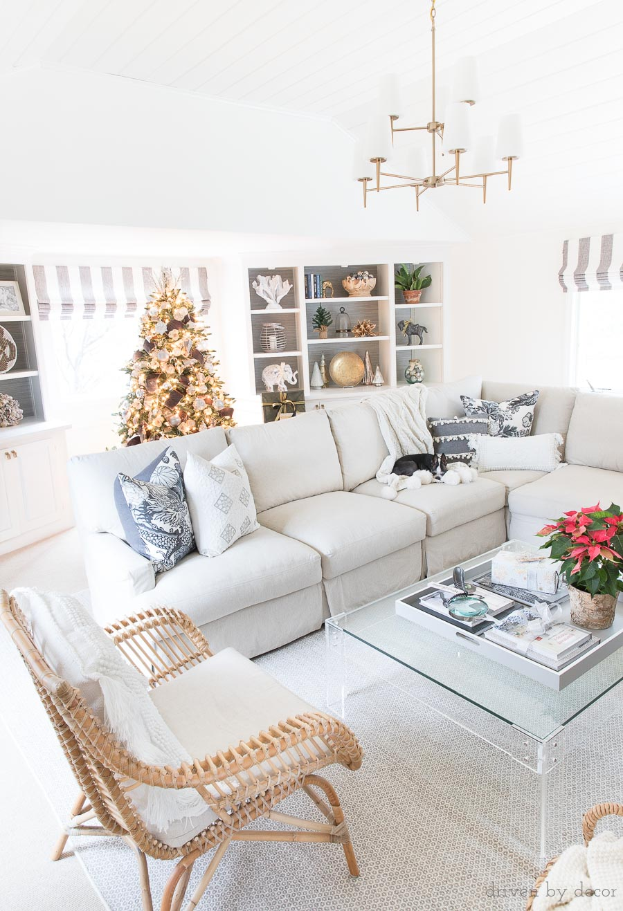 Love this cozy family room decorated for Christmas! Includes two-tiered chandelier, sectional, rattan chair, acrylic coffee table, and more!