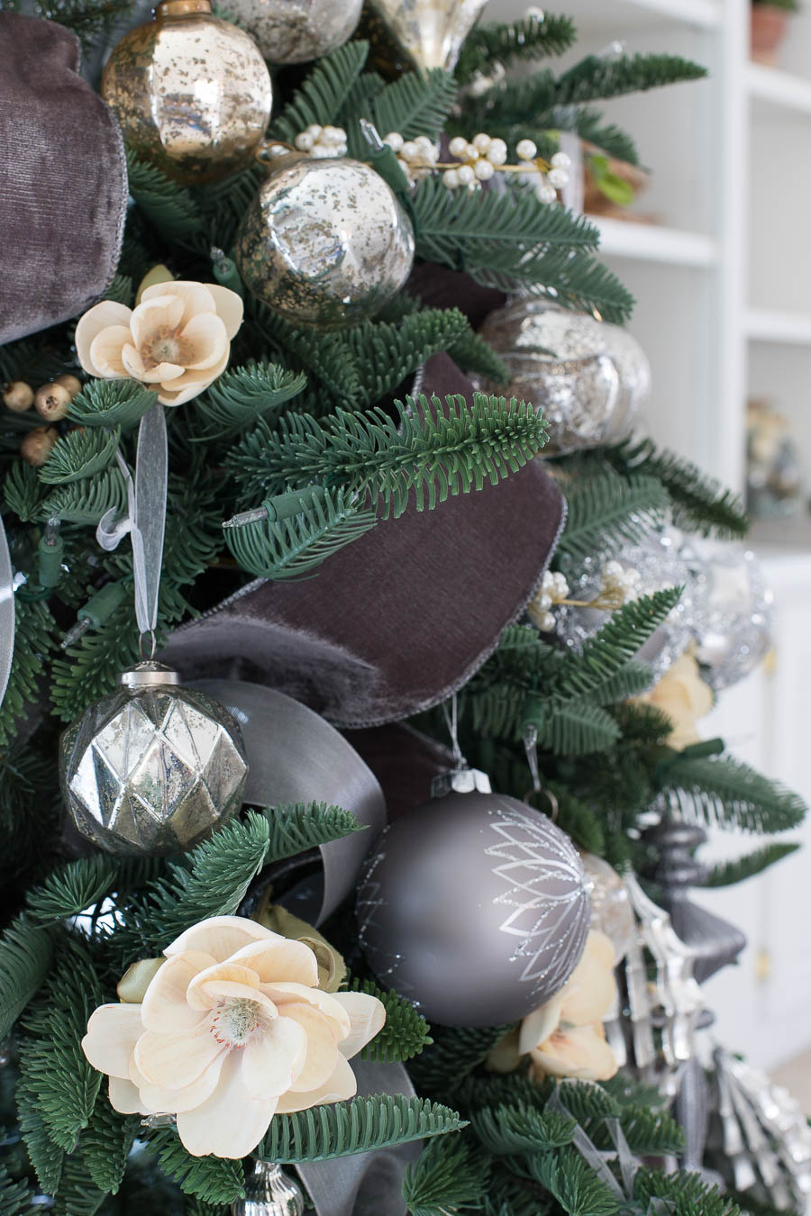 Love how she used faux floral stems along with the velvet ribbon and silver ornaments to decorate her Christmas tree