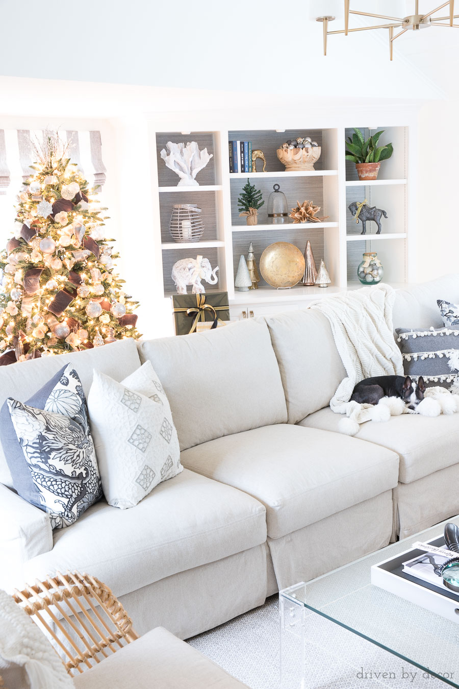 Family room at Christmas with slipcovered sectional, built in bookcases, acrylic coffee table, and a beautiful Christmas tree!