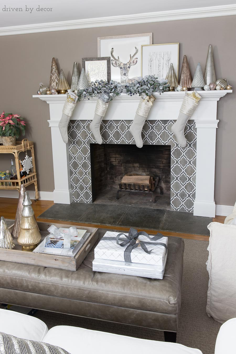 Our fireplace mantel decorated for the holidays with flocked greenery, metallic Christmas trees, layered art, and linen stockings