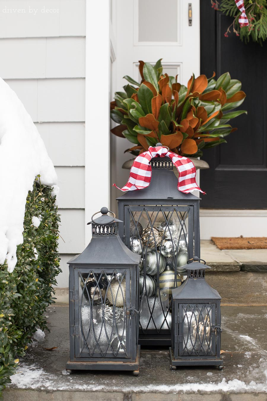 A trio of lanterns filled with ornaments is a simple idea for decorating your porch for Christmas!