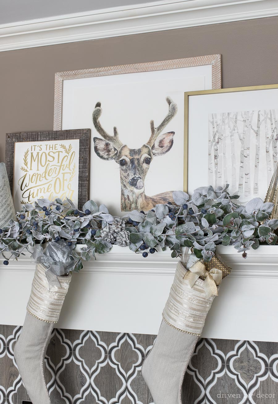 Fireplace mantel decorated for Christmas with layered art and faux frosted eucalyptus branches