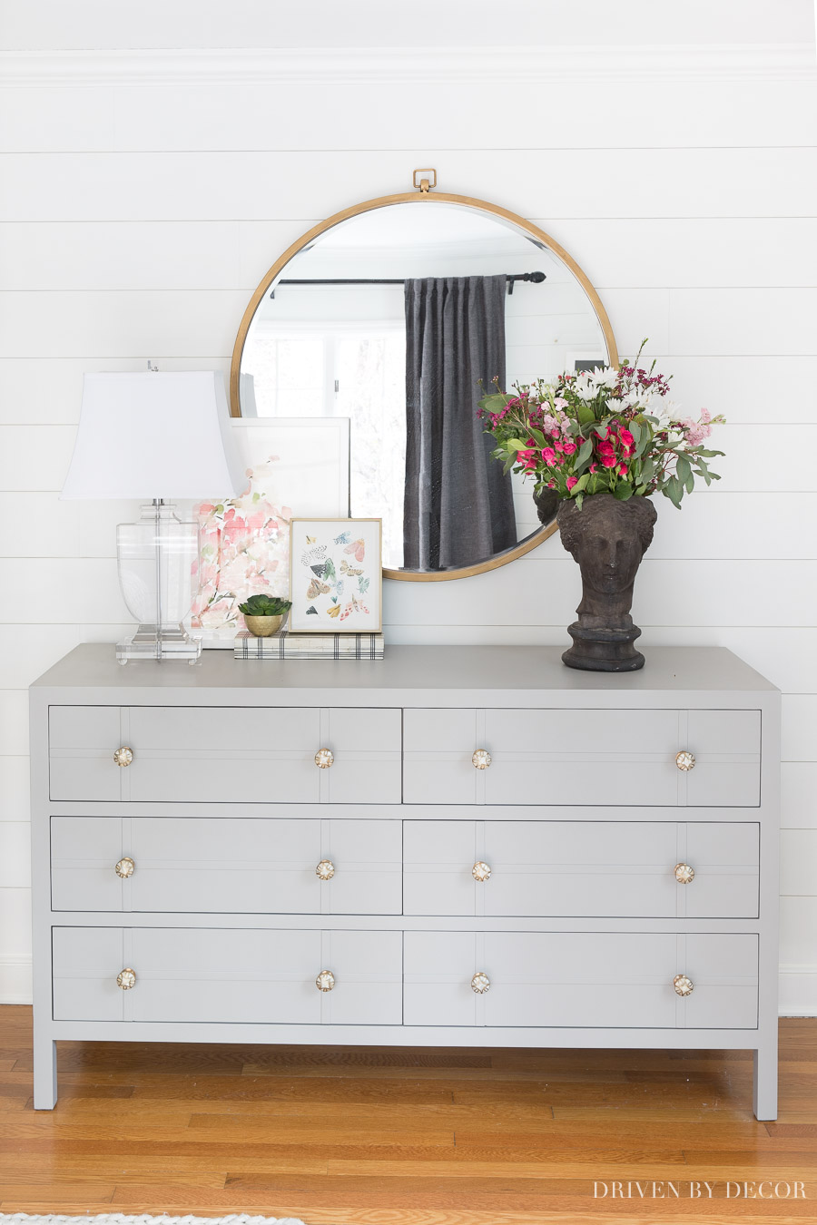 Gray bedroom dresser, large round mirror, and acrylic lamp - perfect for a bedroom!