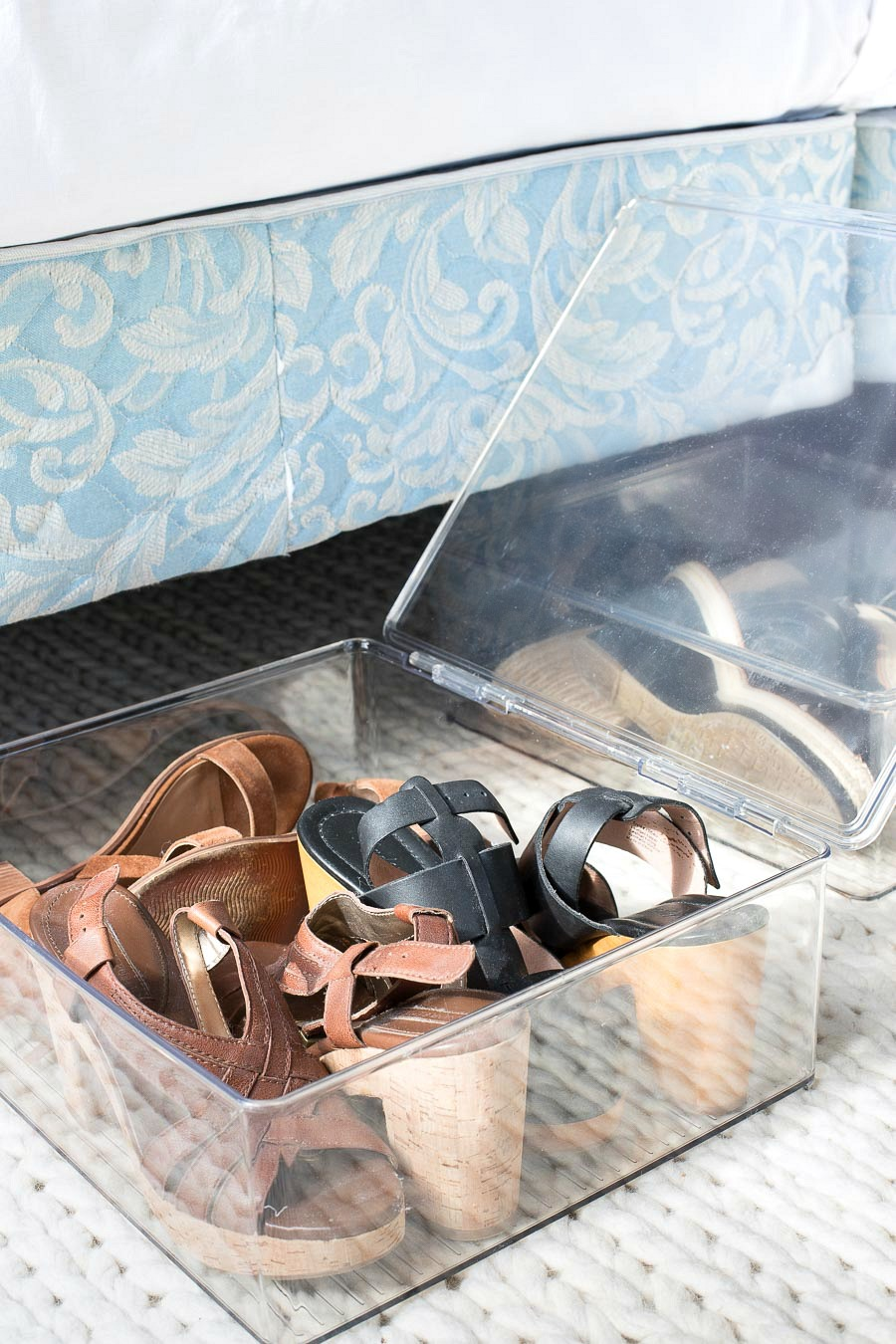 Shoes stored in hinged acrylic boxes that are easily stored under the bed!