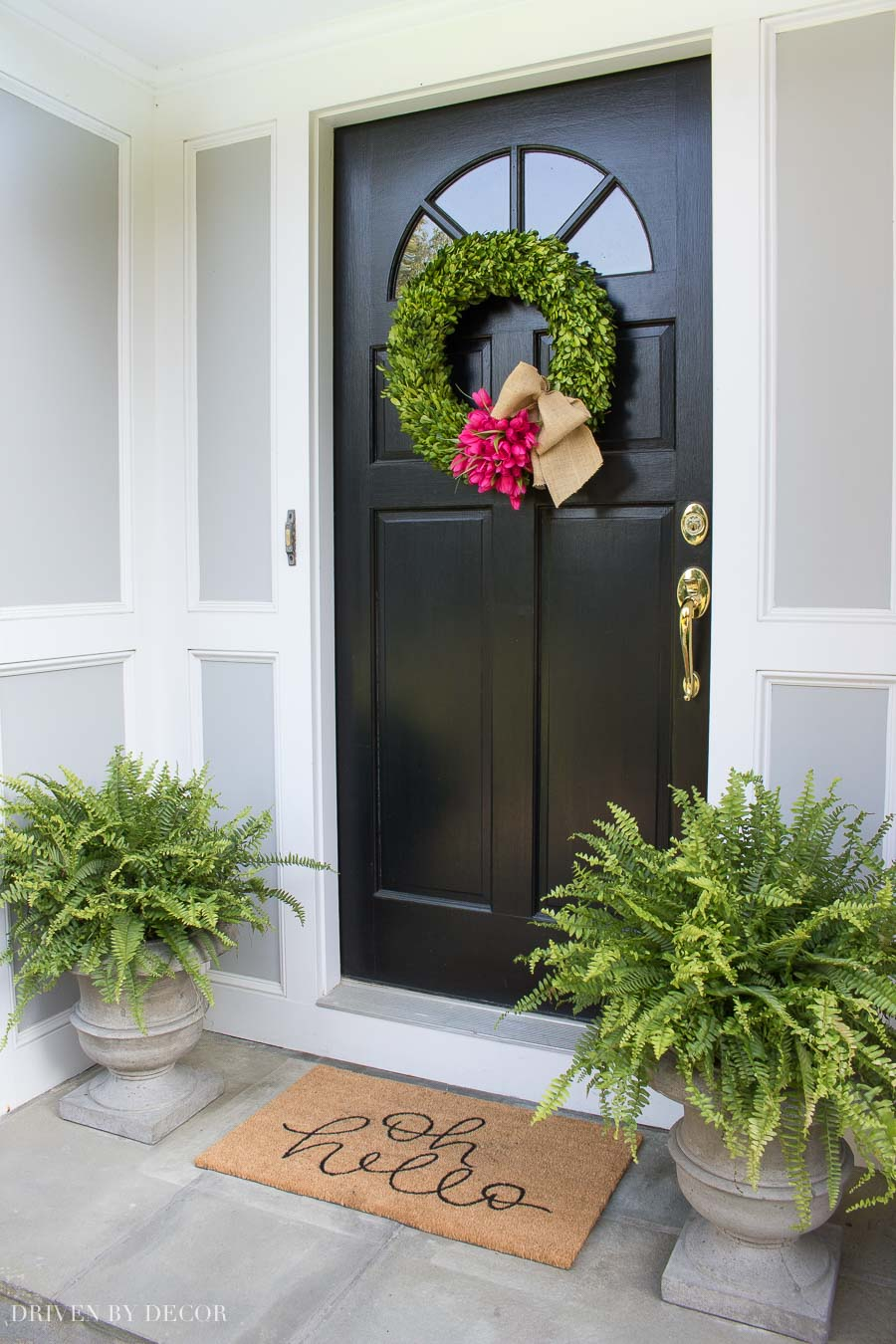 Loving the simple spring door decorations of a boxwood wreath with tulips and planters with Boston ferns!
