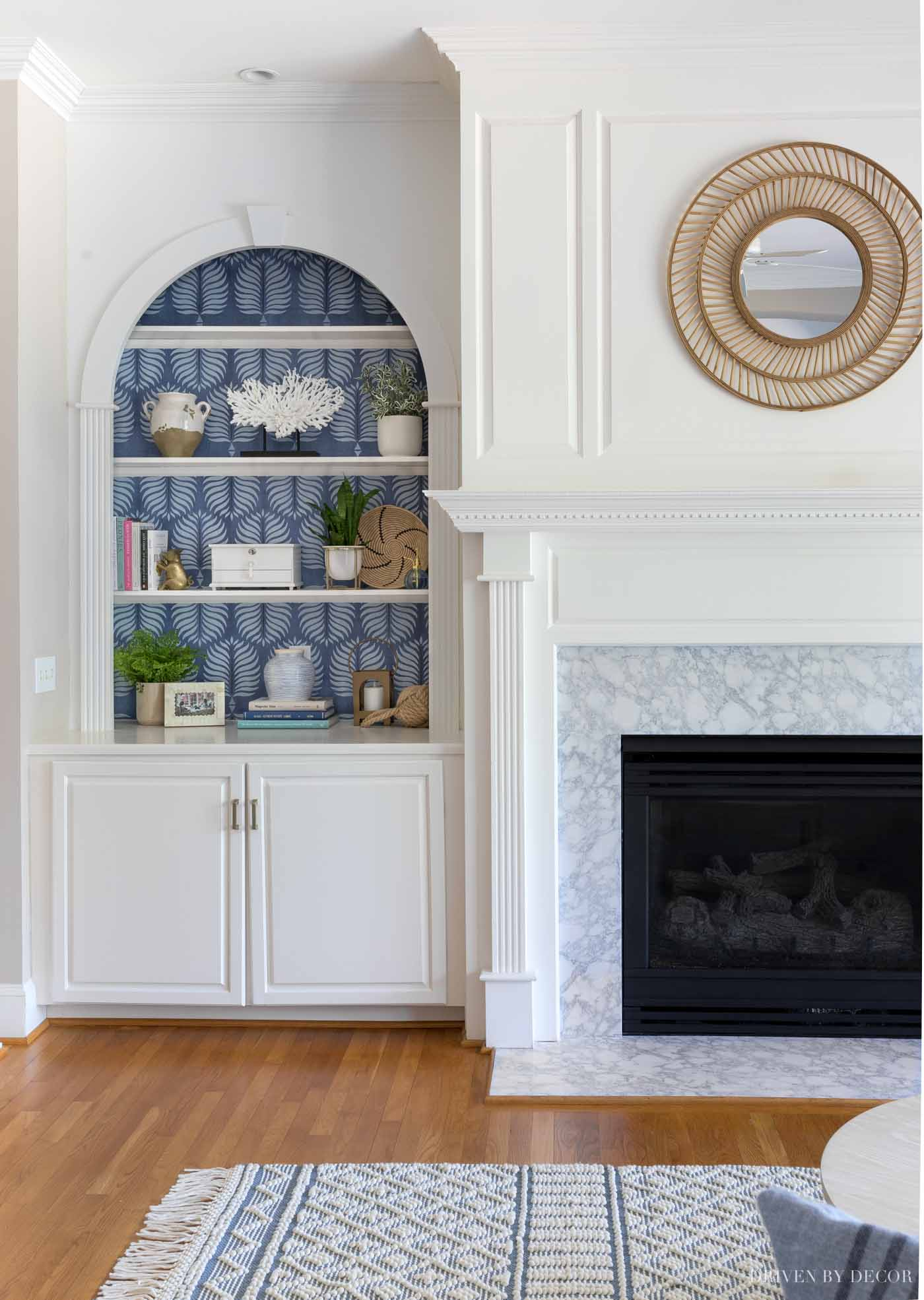 Love the look of a simple rattan mirror above the fireplace!