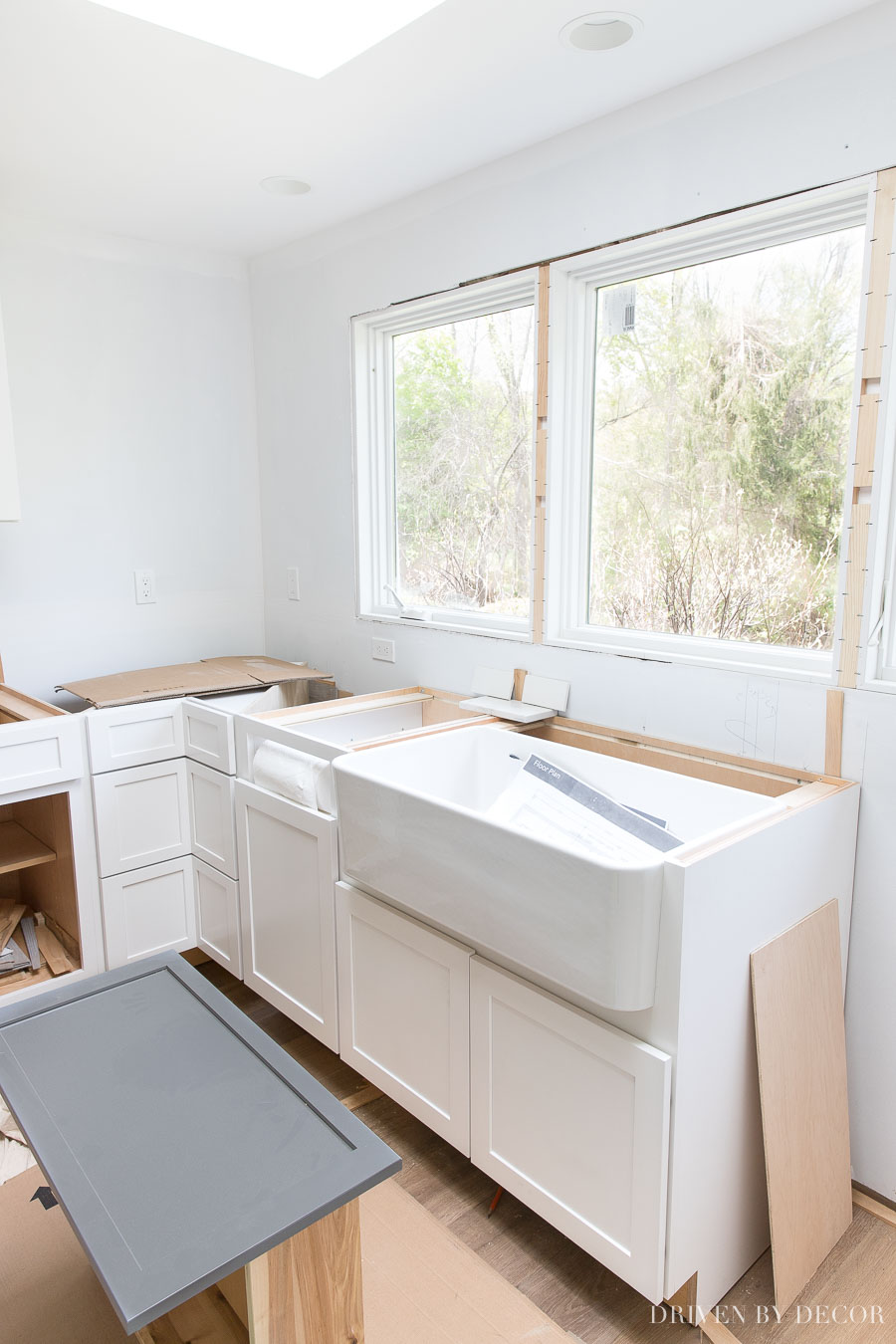Dreamy farmhouse kitchen sink in front of large window - love!