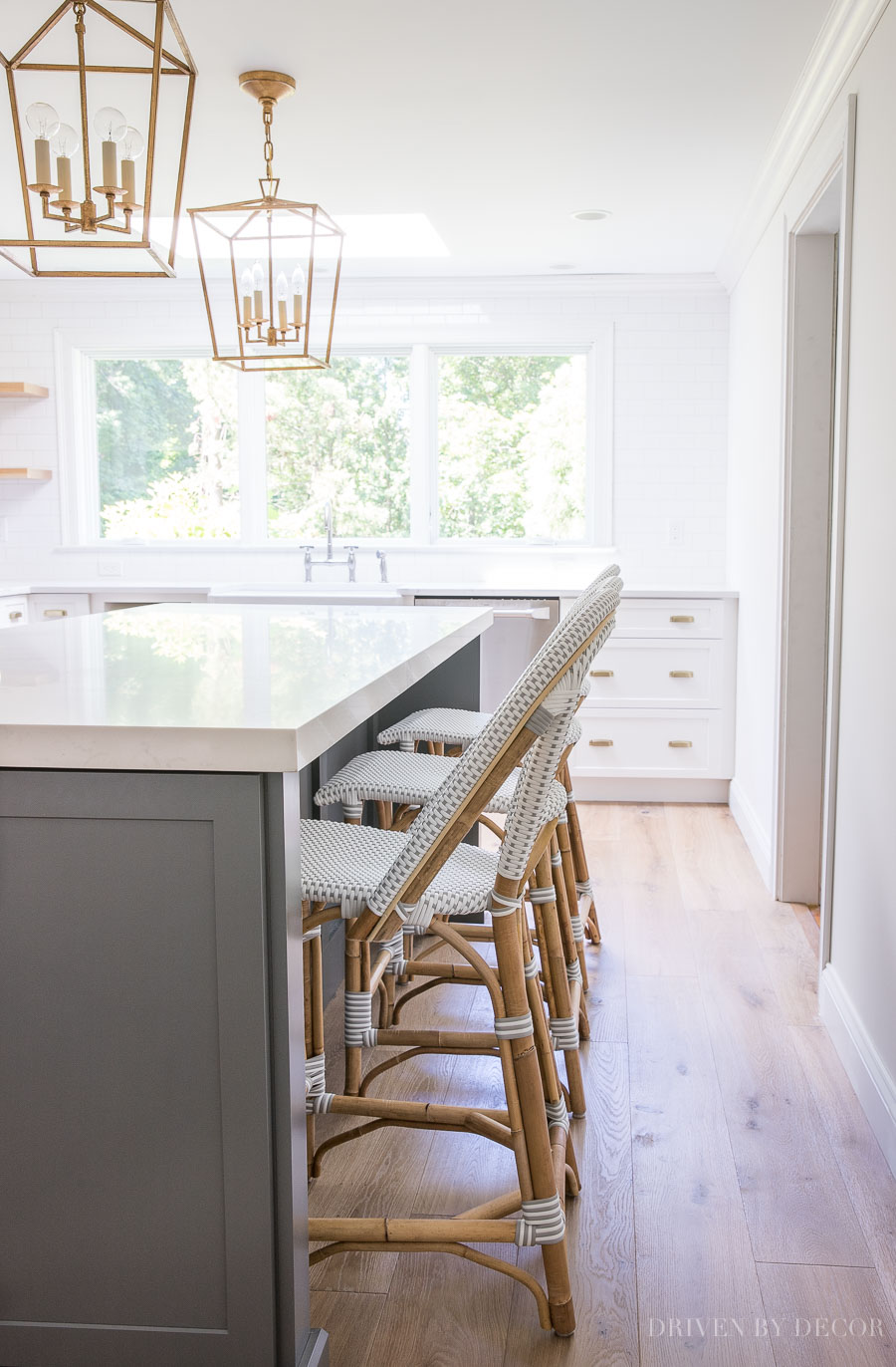 Dark gray kitchen island with woven counter stools and brass light fixtures