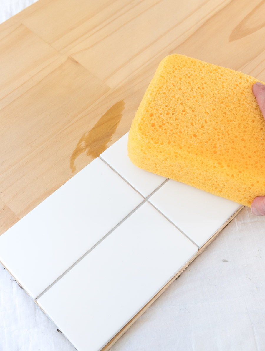 Use a sponge as a final step to clean your tile and remove excess grout - the last step in creating a tile sample board to choose your grout color!