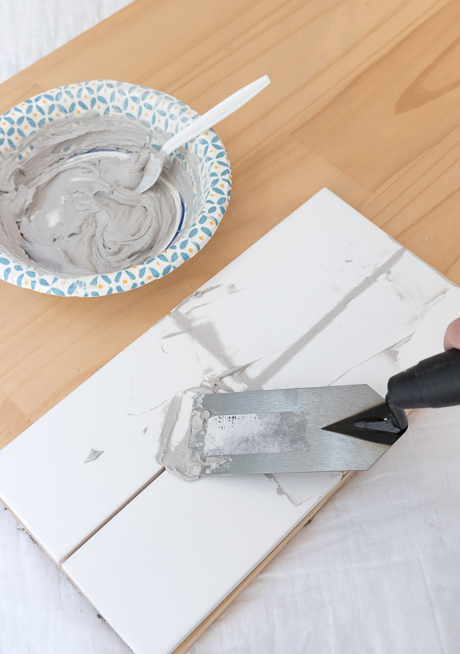 Applying grout to grout sample tiles - I great way to choose the best gray grout for your white subway tile!