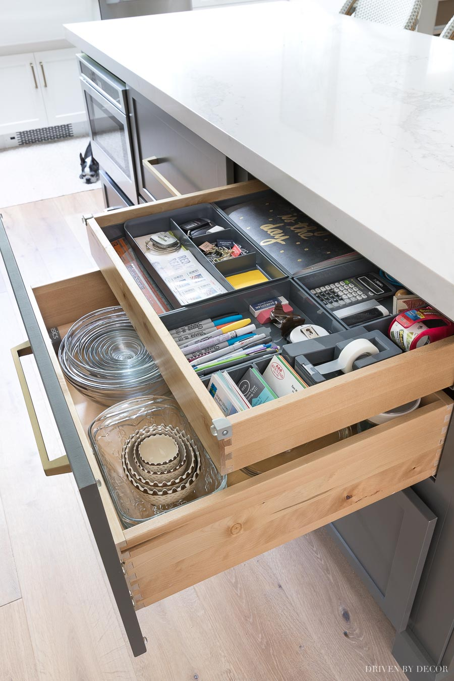 The perfect way to keep desk supplies in your kitchen! This island has a large drawer with a shallow roll out tray! So smart!