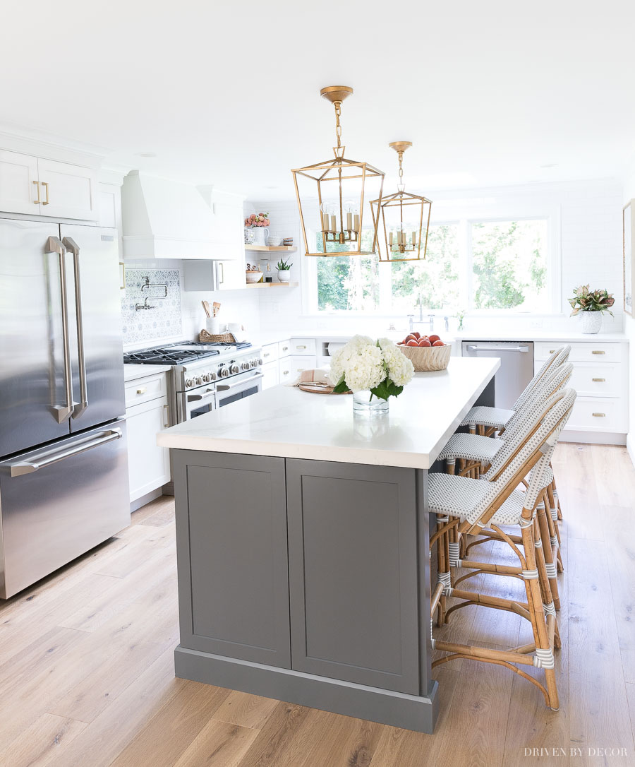 Love this newly remodeled kitchen with gray and white cabinets and brass accents! Such a huge difference from what it looked like before!