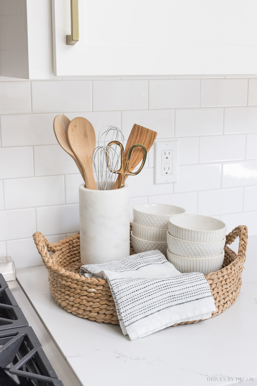 The perfect set-up for next to your range! A round woven tray holds most-used utensils in a pretty marble holder, a hand towel, and white patterned bowls!