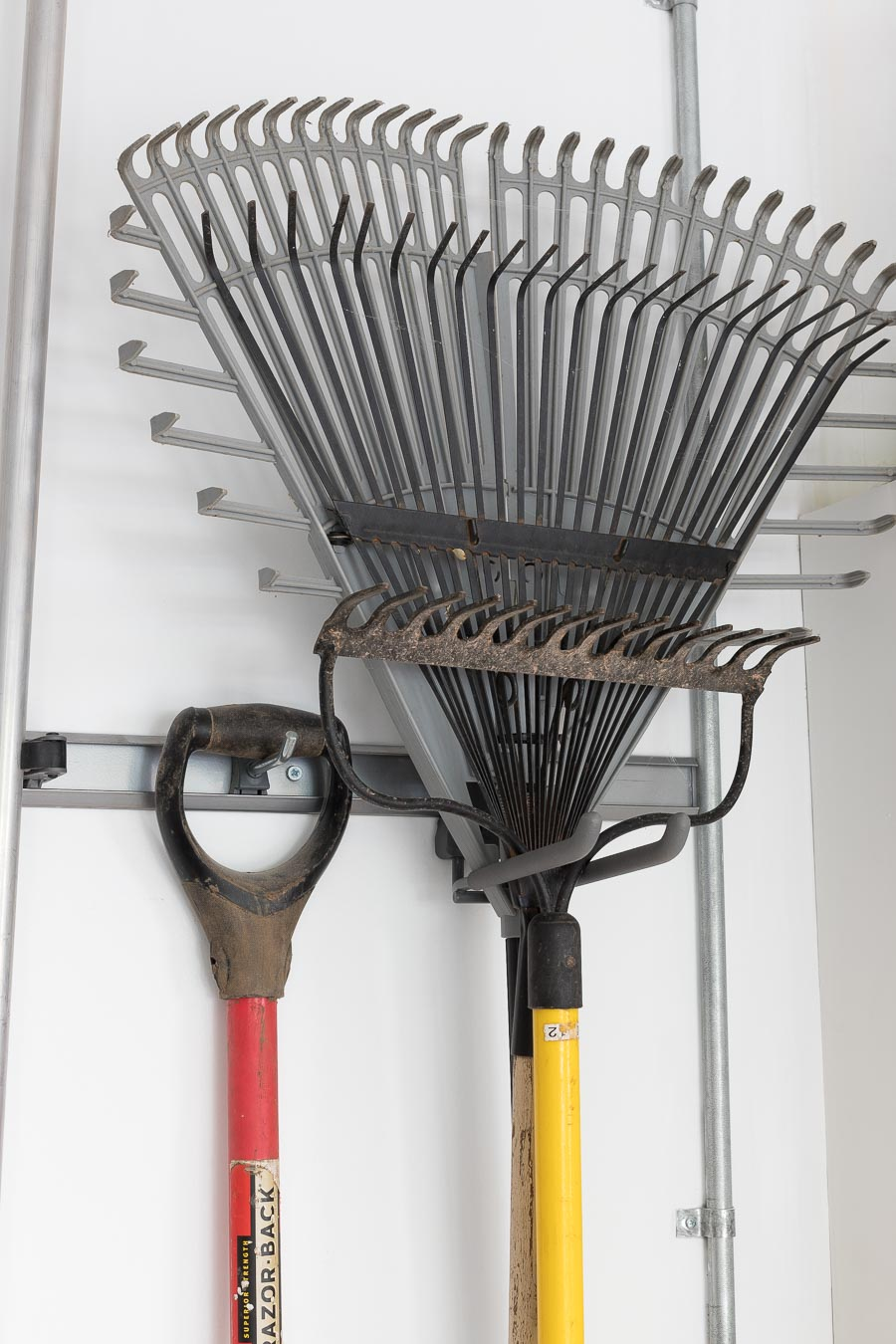 Elfa hooks for hanging long handled tools in the garage - love this organization system!