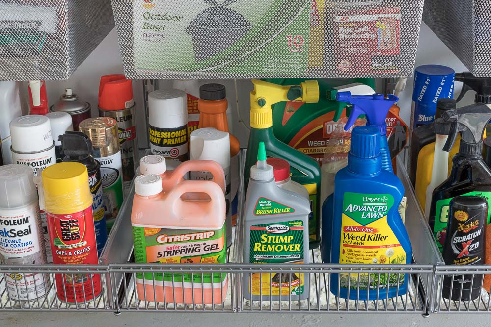 Efla shelf baskets neatly organize all of the bottles and spray cans in this newly organized garage!