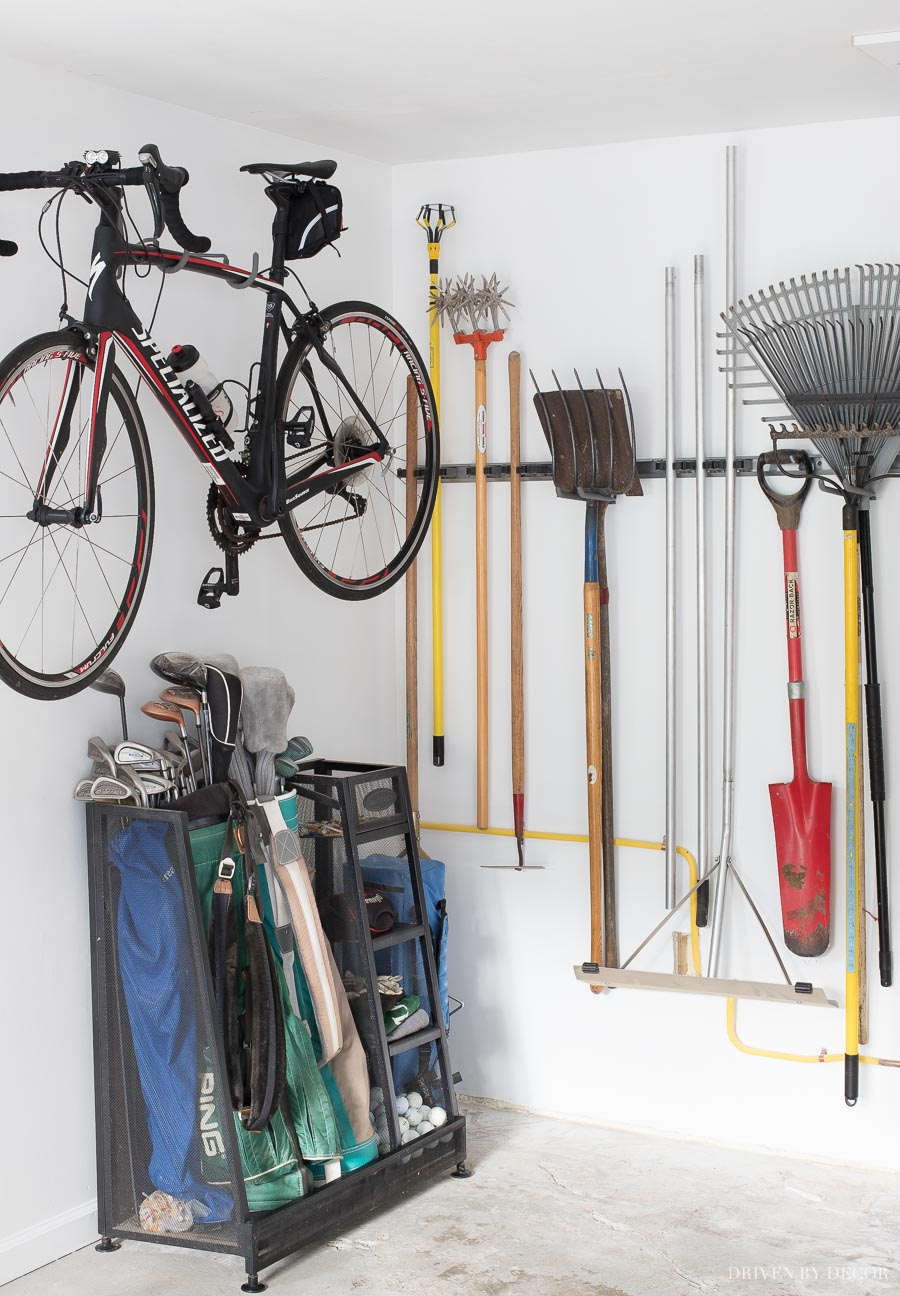 Smart ideas for storing your long handled tools, golf bags, and bike as part of a garage organization project!