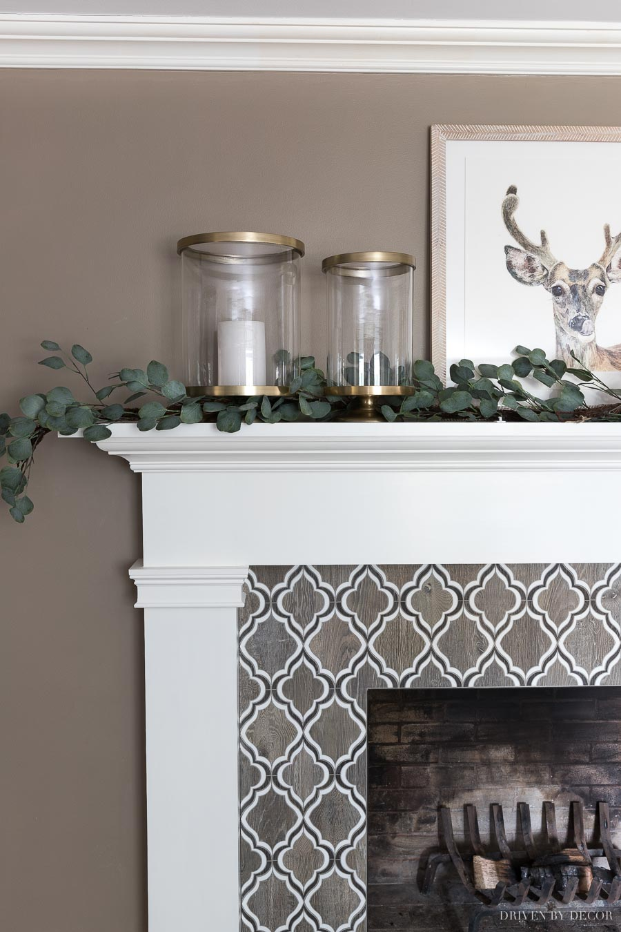 Gorgeous brass hurricanes and eucalyptus garland decorating this fireplace mantel for Christmas!