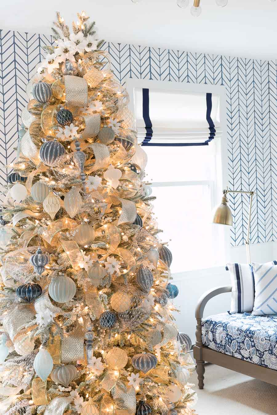 Gorgeous Christmas tree decorated in blue, white, silver, and gold with white poinsettia accents