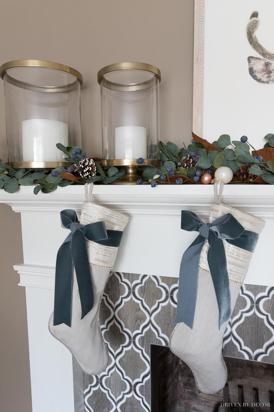Our fireplace mantel at Christmas with brass hurricanes and a eucalyptus garland