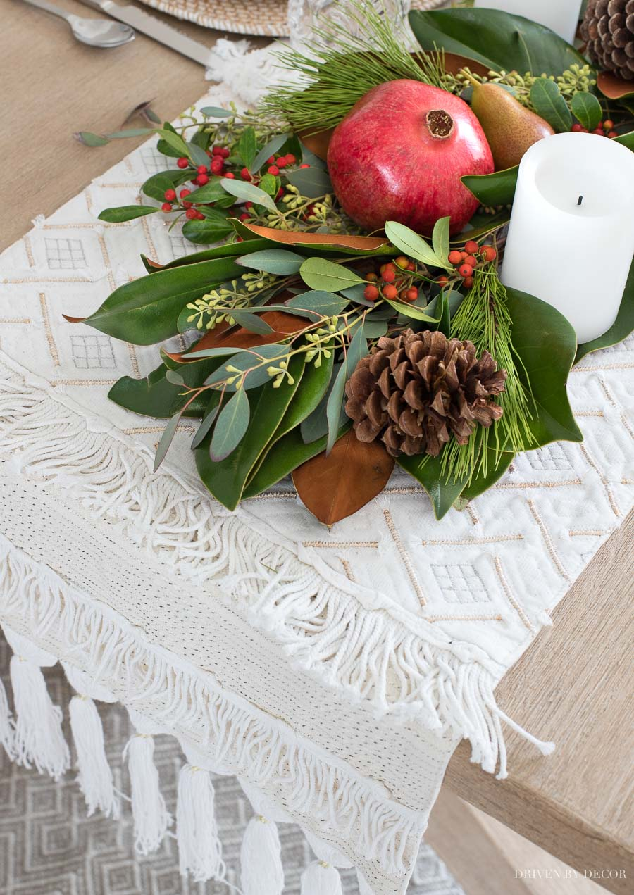 Gorgeous fringed table runner used as a base for a runner made of greenery, fruit, and pinecones.