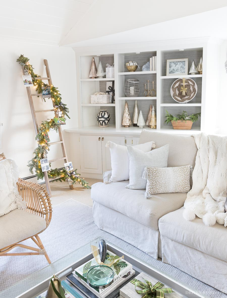 Loving this idea for displaying Christmas cards in our living room - cards are tied on a garland wrapped around a whitewash ladder!